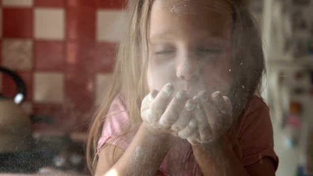 young girl blowing flour in kitchen - birichinata video stock e b–roll