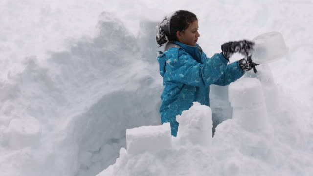 Young girl builds snow fort, in deep drift Mt Washington ski area, Vancouver Island, B.C. fort stock videos & royalty-free footage
