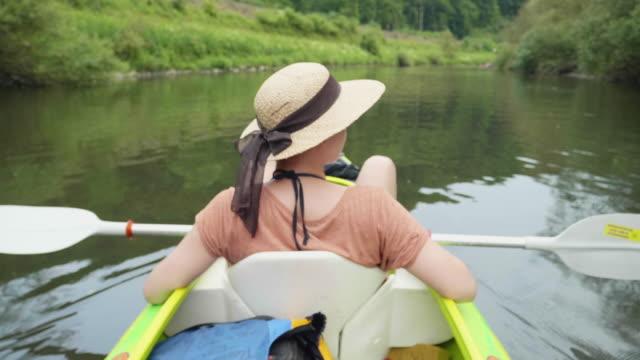 Junges Mädchen an einem wunderschönen See Kanu und entspannen in der Sonne – Video