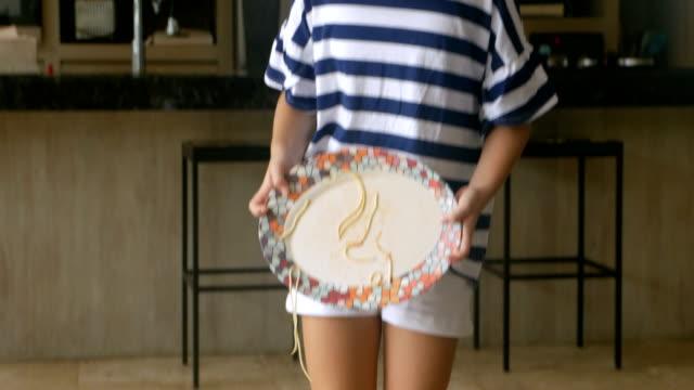 vidéos et rushes de une jeune fille portant une plaque de spaghetti le renverse accidentellement sur le plancher - spaghetti renversé