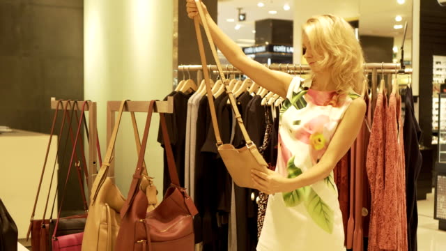 young girl chooses and tries on handbags in a clothing store. - modella negozio video stock e b–roll
