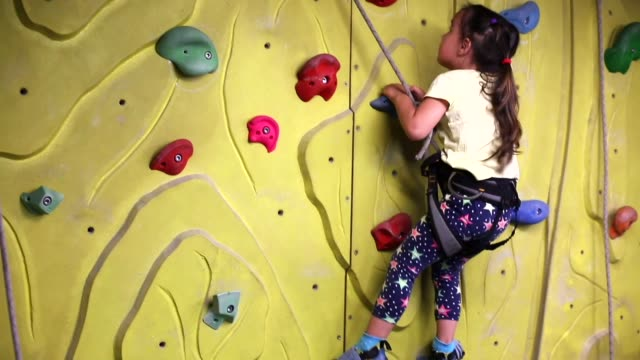 young girl climbing up on an indoors climbing wall - vivere semplicemente video stock e b–roll