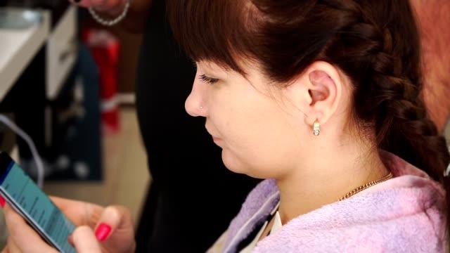 スマート フォンでの翻訳の助けを借りて美容師と若い女の子通信します。 - 美容院点の映像素材/bロール