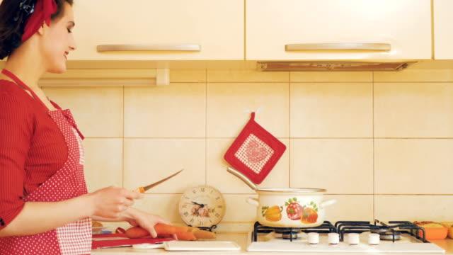 Menina corta cenoura na tábua de cozinha - estilo pin-up - vídeo