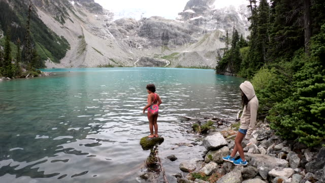 young girl dabbles toes in cold, crystal clear mountain lake - pantaloncini video stock e b–roll