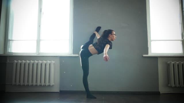 ung flicka dansare gör stretching. värma upp före träning - balettstång bildbanksvideor och videomaterial från bakom kulisserna