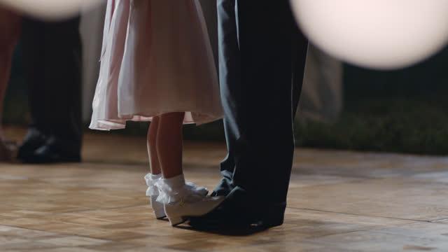 若い女の子は結婚披露宴できらめくライトの下で父親の足で踊ります。 - 娘点の映像素材/bロール