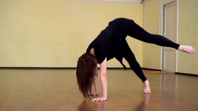 ung flicka dans i studion. hon repeterar. praktiseras rörelse för fötterna, som hon snart dans konkurrens. - gympingdräkt bildbanksvideor och videomaterial från bakom kulisserna