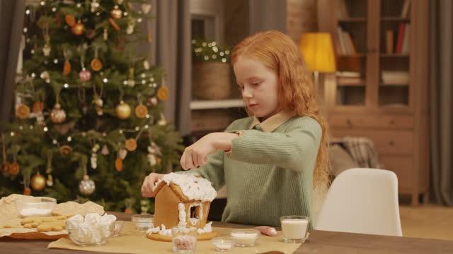 ung flicka dekorera pepparkakor hus - pepparkaka bildbanksvideor och videomaterial från bakom kulisserna