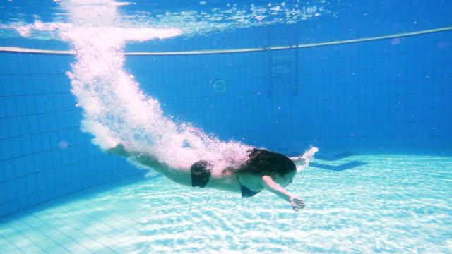 Chica joven de buceo en piscina - vídeo