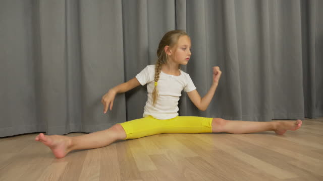Young girl do split and stretching at living room indoors. Happy young girl dancing and sitting.