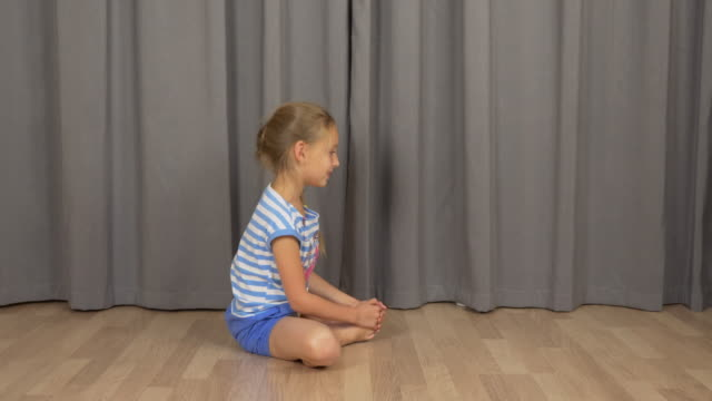 Young girl do yoga butterfly pose. White girl stretchin at living room indoors. video