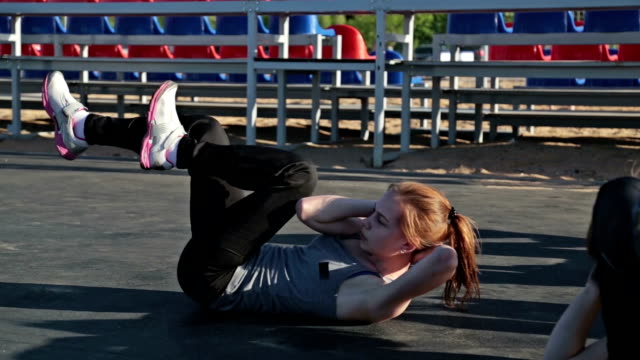 Young girl doing sit-ups exercising together video