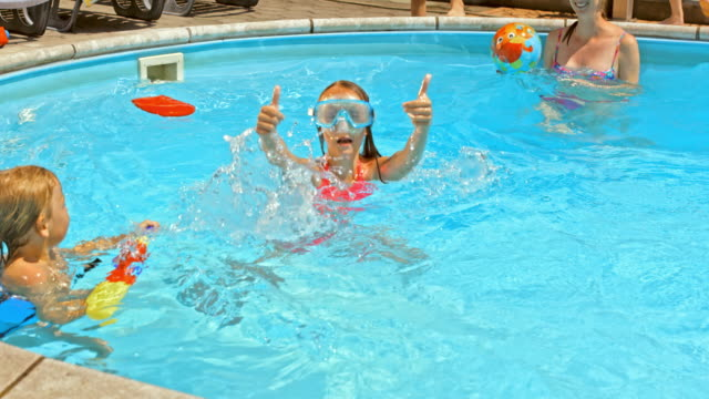 vídeos de stock e filmes b-roll de câmara lenta jovem dando polegares para cima na festa de piscina - brinquedos na piscina