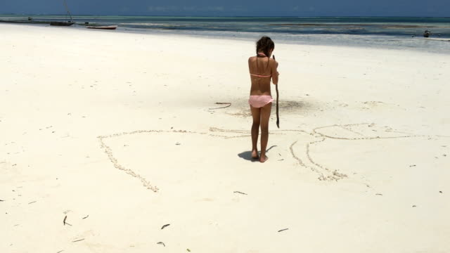 Young Girl Drawing in Sand on Beach of Tropical Island Young Girl Drawing in Sand on Beach of Tropical Island. tanzania stock videos & royalty-free footage