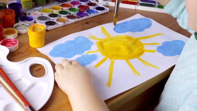Young girl drawing yellow sun and blue clouds