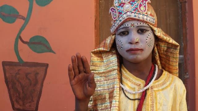女神の顔を描いた片手でカメラに向かって与える恵みに扮した少女発生ハンドヘルド - 舞台化粧点の映像素材/bロール