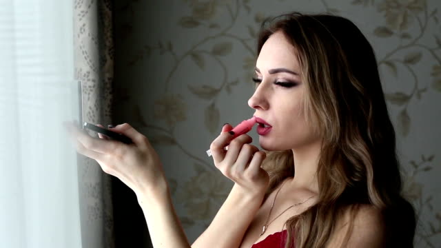 ung flicka klädd i röda underkläder gör makeup nära ett fönster hemma., - endast flickor bildbanksvideor och videomaterial från bakom kulisserna