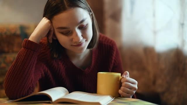 stockvideo's en b-roll-footage met jong meisje drinken van een kopje thee of koffie en het lezen van een boek - comfortabel