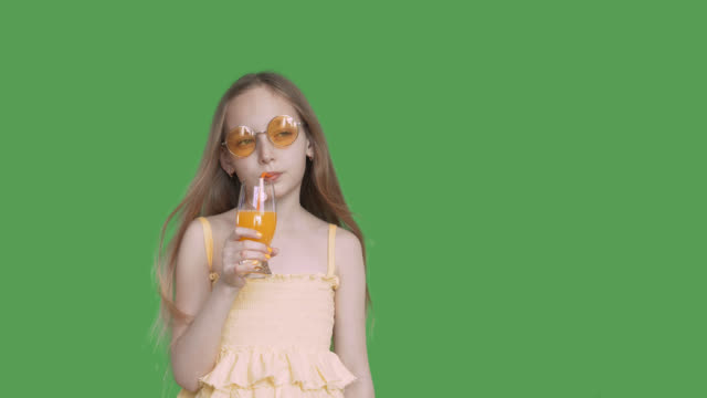 Young girl drinking orange juice from glass by straw on green background. Teenager girl drinking fruit cocktail on transparent green background. Alpha channel, keyed green screen.
