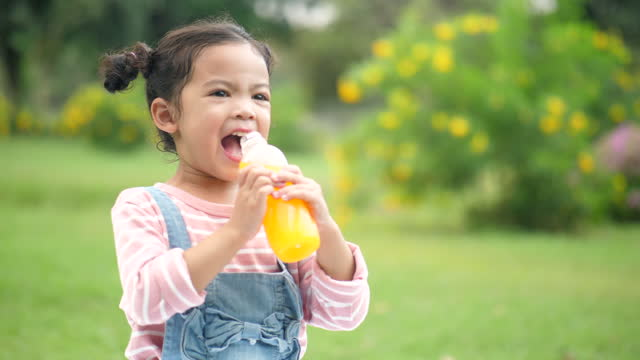 Young girl Drinking Orange Juice young girl thirsty in the plat fields orange juice stock videos & royalty-free footage
