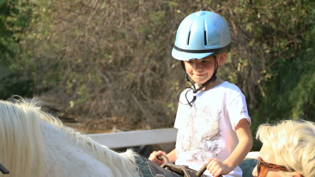 Young girl during horse riding lesson video