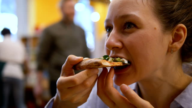 Young girl eating juicy hot slice of pizza
