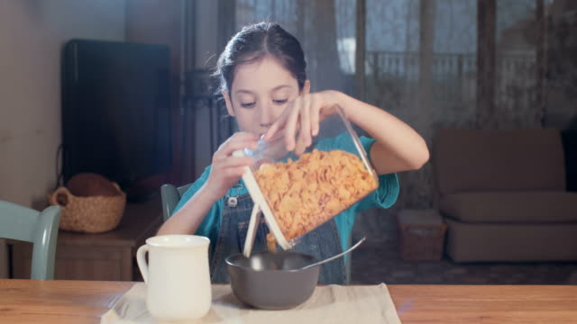 young girl eating morning cereal with milk video
