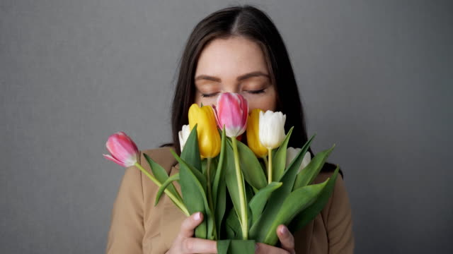 young girl enjoy a bouquet of tulips. - marzo video stock e b–roll