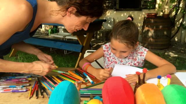 vídeos de stock, filmes e b-roll de jovem, desfrutando de desenho ao ar livre enquanto assistências da mãe dela - arte e artesanato assunto