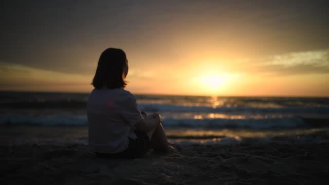 vídeos de stock, filmes e b-roll de rapariga que aprecia o por do sol na praia - pôr do sol