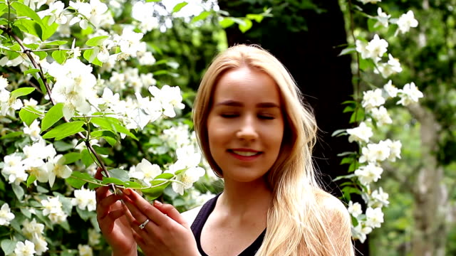 Young girl enjoys blossoming of white flowers in garden video