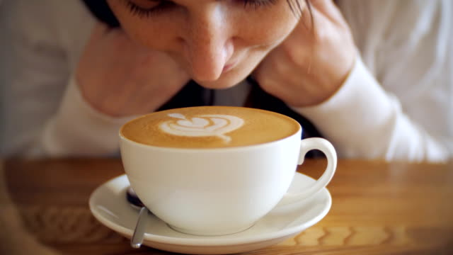 Young girl enjoys the aroma of delicious coffee, selective focus