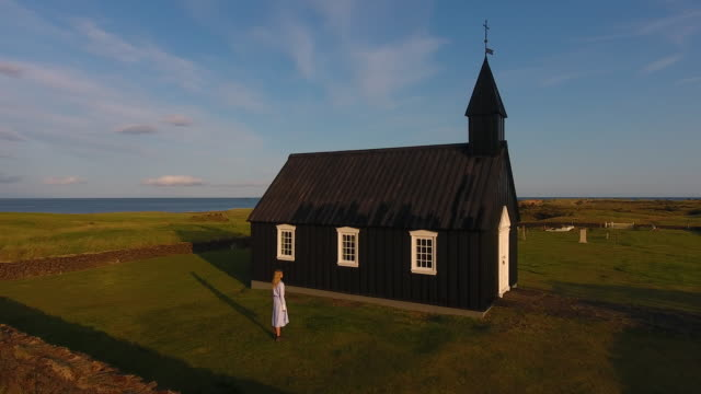 A young girl explores a black church in Iceland. Fairytale Fashion Story - video