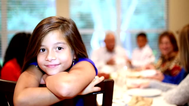 Young girl, family at Thanksgiving dinner table.