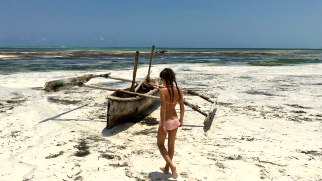 Young Girl Finding a Wooden Catamaran on Sandy Beach on Tropical Island Young Girl Finding a Wooden Catamaran on Sandy Beach on Tropical Island. tanzania stock videos & royalty-free footage
