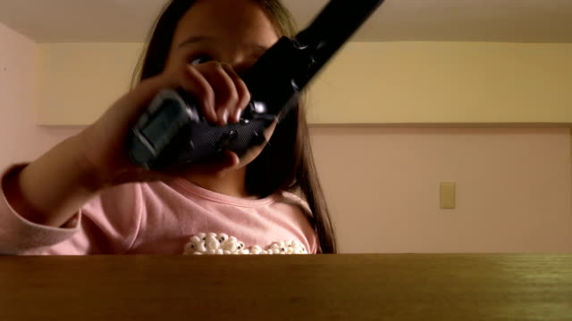 Young girl finds gun in closet Young girl climbs and finds gun in cupboard and carries it down gun stock videos & royalty-free footage