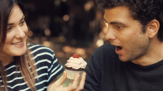 giovane ragazza dà un lampone dolce cupcake per il suo fidanzato - cupcake video stock e b–roll