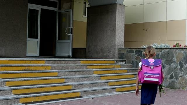 Niña ir a la escuela caminando por escalera vienen en a entrada de la escuela. Regresar al concepto de escuela. 1 chica de septiembre con mochila subid a la puerta de la escuela. Cámara en mano disparó verano día de otoño. - vídeo