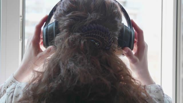 en ung flicka går till fönstret och sätter på sig hörlurarna för att lyssna på musik. en kvinna njuter av melodin i sina hörlurar. - människorygg bildbanksvideor och videomaterial från bakom kulisserna