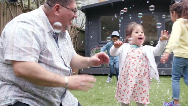 vídeos de stock e filmes b-roll de young girl having fun in the garden with her family - capacidades diferentes
