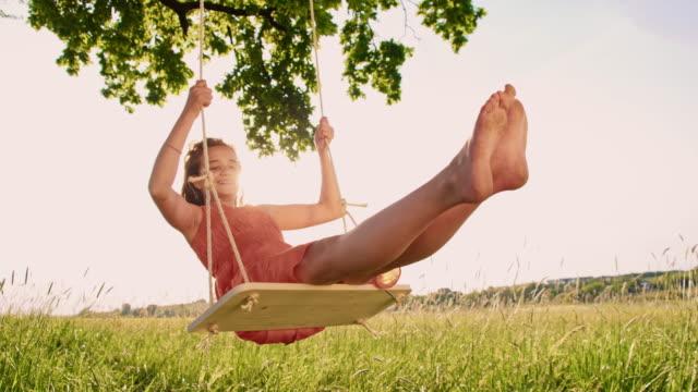 giovane ragazza che si diverte fiore su un albero altalena - scalzo video stock e b–roll
