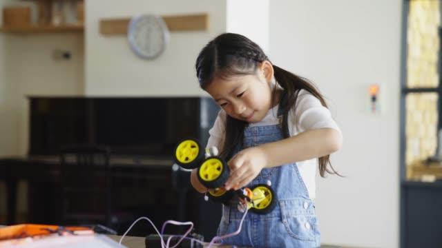 молодая девушка весело работает над дизайном робота - манипулятор робота производственное оборудование стоковые видео и кадры b-roll
