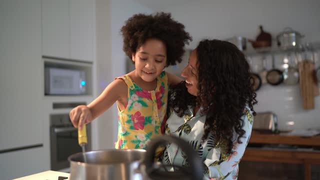 ung flicka som hjälper mamma matlagning hemma - tema bildbanksvideor och videomaterial från bakom kulisserna