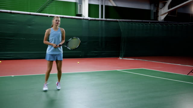 Young girl hitting ball with racket playing tennis on court video