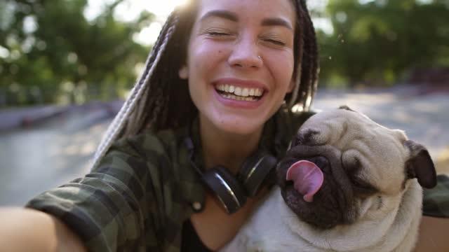 vídeos de stock, filmes e b-roll de jovem segurando seu cachorro. um cachorrinho de pug bege bonito está tentando lamber a cara. uma mulher segura a câmera - alegria
