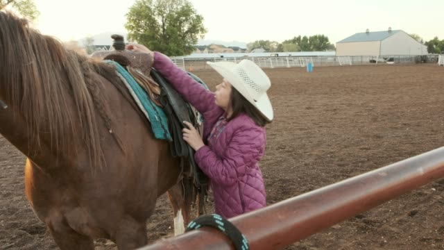 Young Girl Horseback Riding Young girls prepare and ride horses in the morning on a ranch. saddle stock videos & royalty-free footage