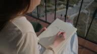 istock Young girl illustrator drawing portrait on balcony 1255950813