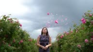 istock Young girl in a blue dress throwing pink roses in the sky 1277086292