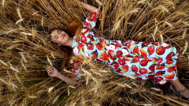 buğday alan ve gülümser elbiseli genç kız yatıyor - çavdar stok videoları ve detay görüntü çekimi